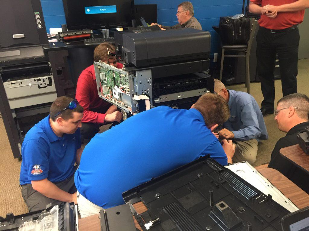 technicians take apart copiers